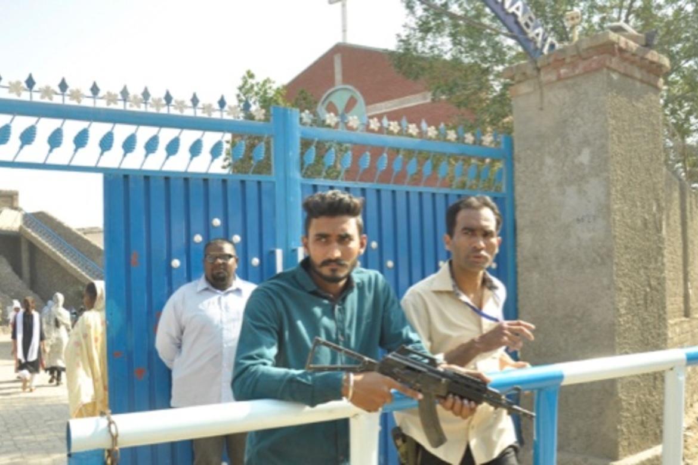 Sikander ved porten og flere væpnede vakter passer på ved inngangen til St Johannes katolske kirke i Youhanabad i Lahore i Pakistan.