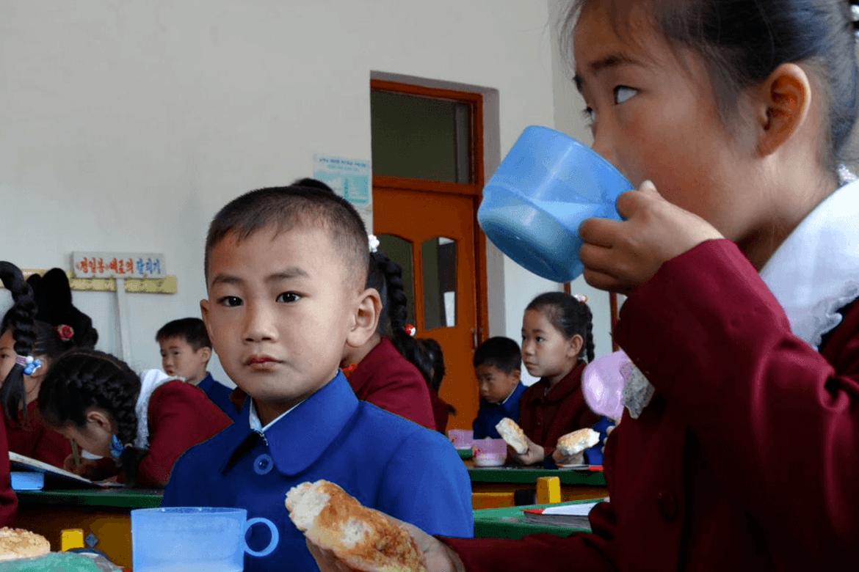 På rekke og rad sitter barna lydige og venter. De spiser sine boller når de får beskjed om det.