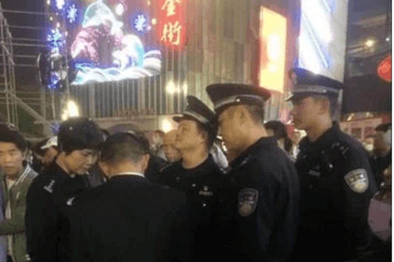 Her forstyrrar kinesisk politi ei juleførestelling med julesangar på Wanda-torget i byen Xiamen.  Foto frå Twitter