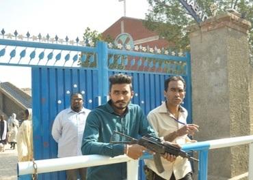 Sikhander står ved porten han beskyttet med sitt eget liv da terroristene slo til i mars 2015. Her sammen med væpnede vakter.