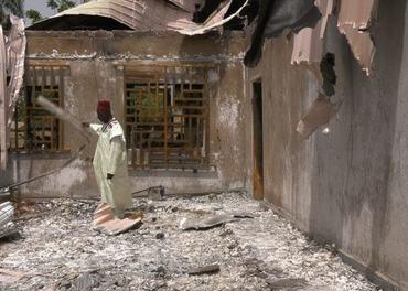 Ein kristen landsbyhovding studerer sitt øydelagde hus.