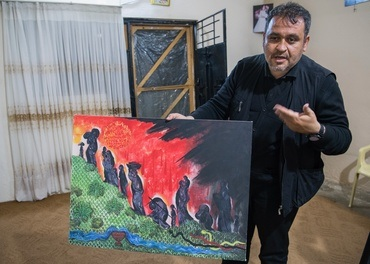 Fader Samir i den kaldeisk-katolske kyrkja i landsbyen Enishke i den kurdiske regionen i Irak viser fram eit bilete laga av ein avdød kunstnar. Kristne er på veg mot sitt Golgata, slangen er IS og andre ekstremistgrupper, elva er Tigris som gir håp.