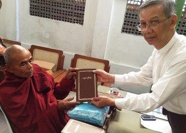 Aung Thet Nyunt gir en buddhistmunk i Myanmar en bibel innbundet i gull og med gullskrift.