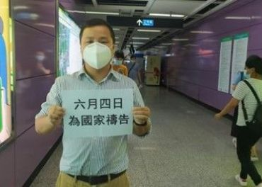 Gao Heng holder opp plakaten som kaller til bønn for Kina 4. juni.