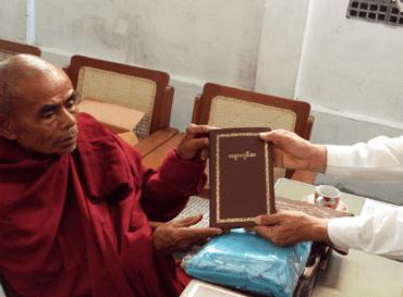 Vårt partner gir en buddhistmunk en bibel med gullskrift.